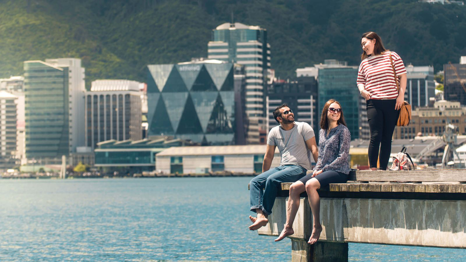 Three smiling students are standing and sitting on the edge of a wharf on Wellington's waterfront.